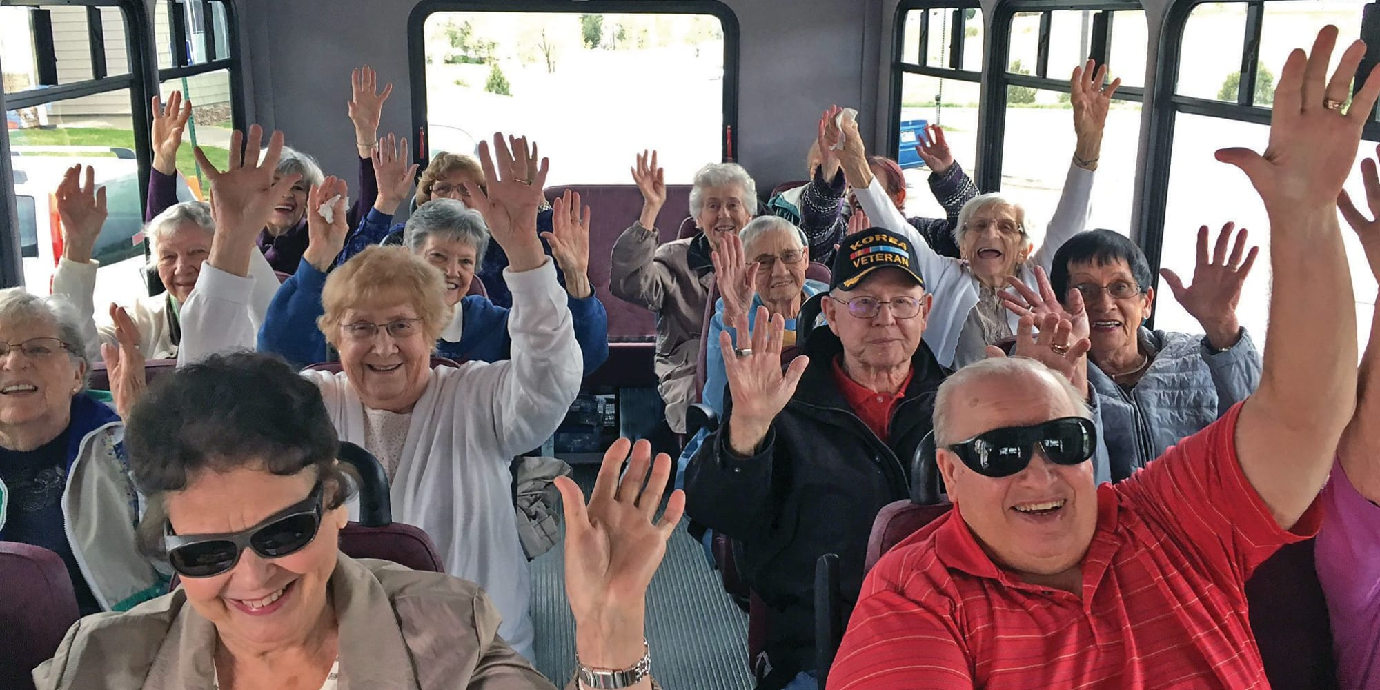 Resident from Summit Glen in Colorado Springs, Colorado with their hands up in the community bus
