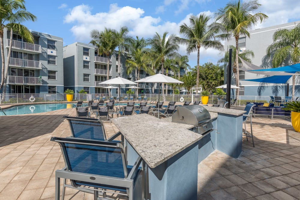 Outdoor grilling area with seating and places to cook poolside at Beach Walk at Sheridan in Dania Beach, Florida