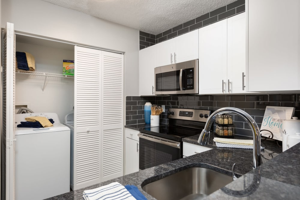 Model kitchen with wash and dryer in unit right near by at Beach Walk at Sheridan in Dania Beach, Florida