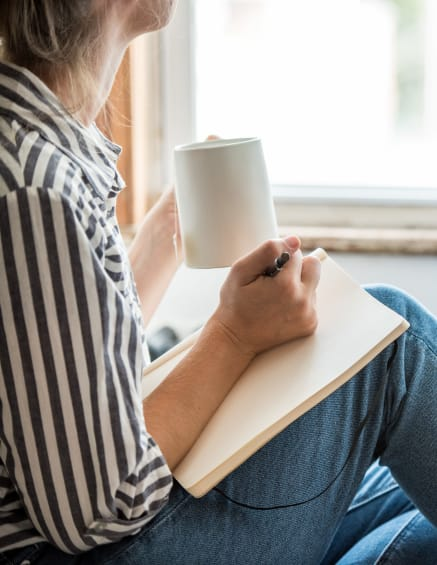 Resident jotting some thoughts down in her journal while sipping on some tea in her new home at Crest at Riverside in Roswell, Georgia
