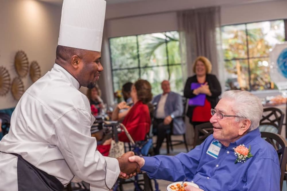 A resident shaking hands with the chef at Atrium at Liberty Park in Cape Coral, Florida