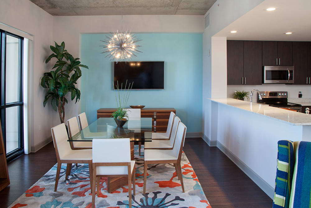 Different take on decor showing dining area and breakfast bar in 55 West Apartments model home