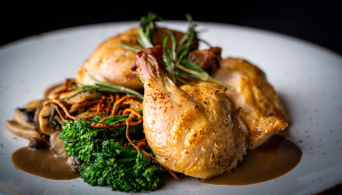 Roasted chicken and greens on a dish at The Springs at Lancaster Village in Salem, Oregon