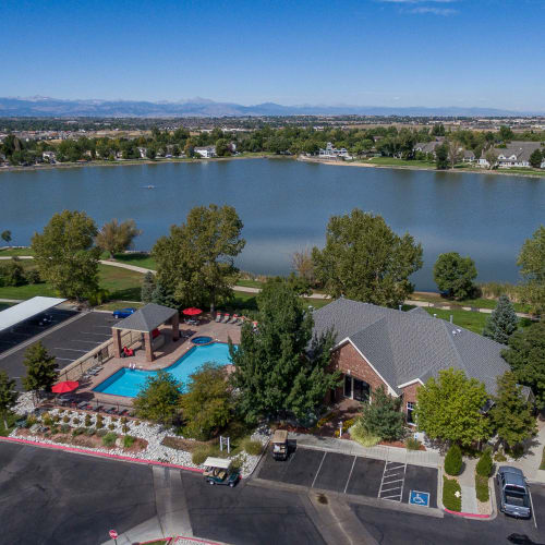 Aerial view of leasing office, pool, and beautiful lake next to property at Promenade at Hunter's Glen Apartments in Thornton