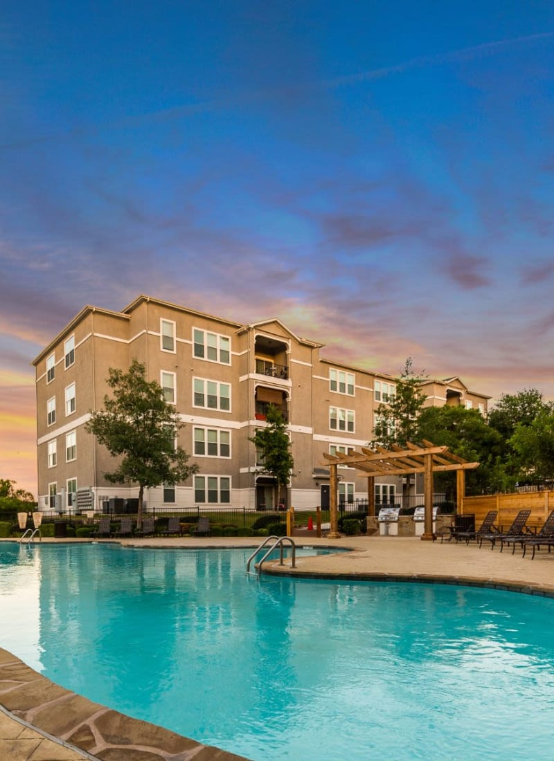 Lit pool at sunset in front of units at Marquis at Crown Ridge in San Antonio, Texas