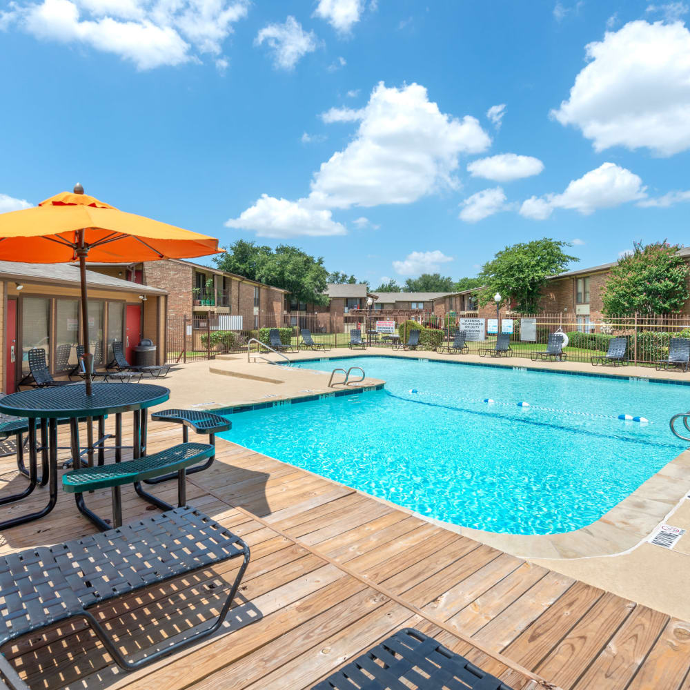 Swimming pool with lounge chairs at 8500 Harwood Apartment Homes in North Richland Hills, Texas
