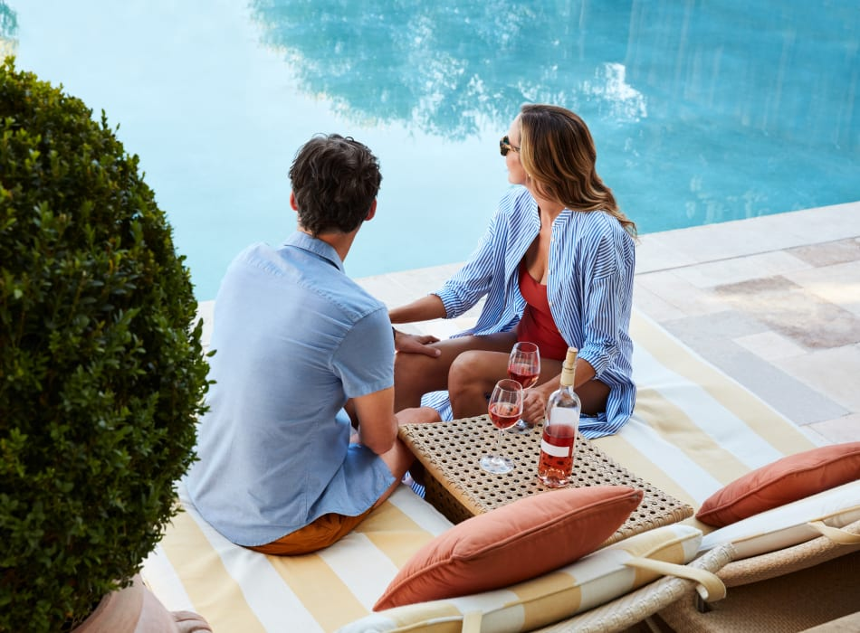 Resident couple enjoying a glass of wine near the pool at Sofi Westview in San Diego, California