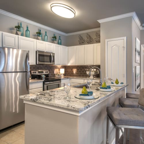 Gourmet kitchen with an island and subway tile backsplash in a model home at Olympus Las Colinas in Irving, Texas