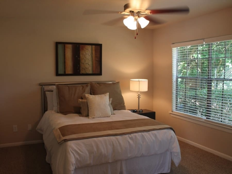 Master bedroom with plush carpeting at The Reserve at Windmill Lakes in Houston, Texas