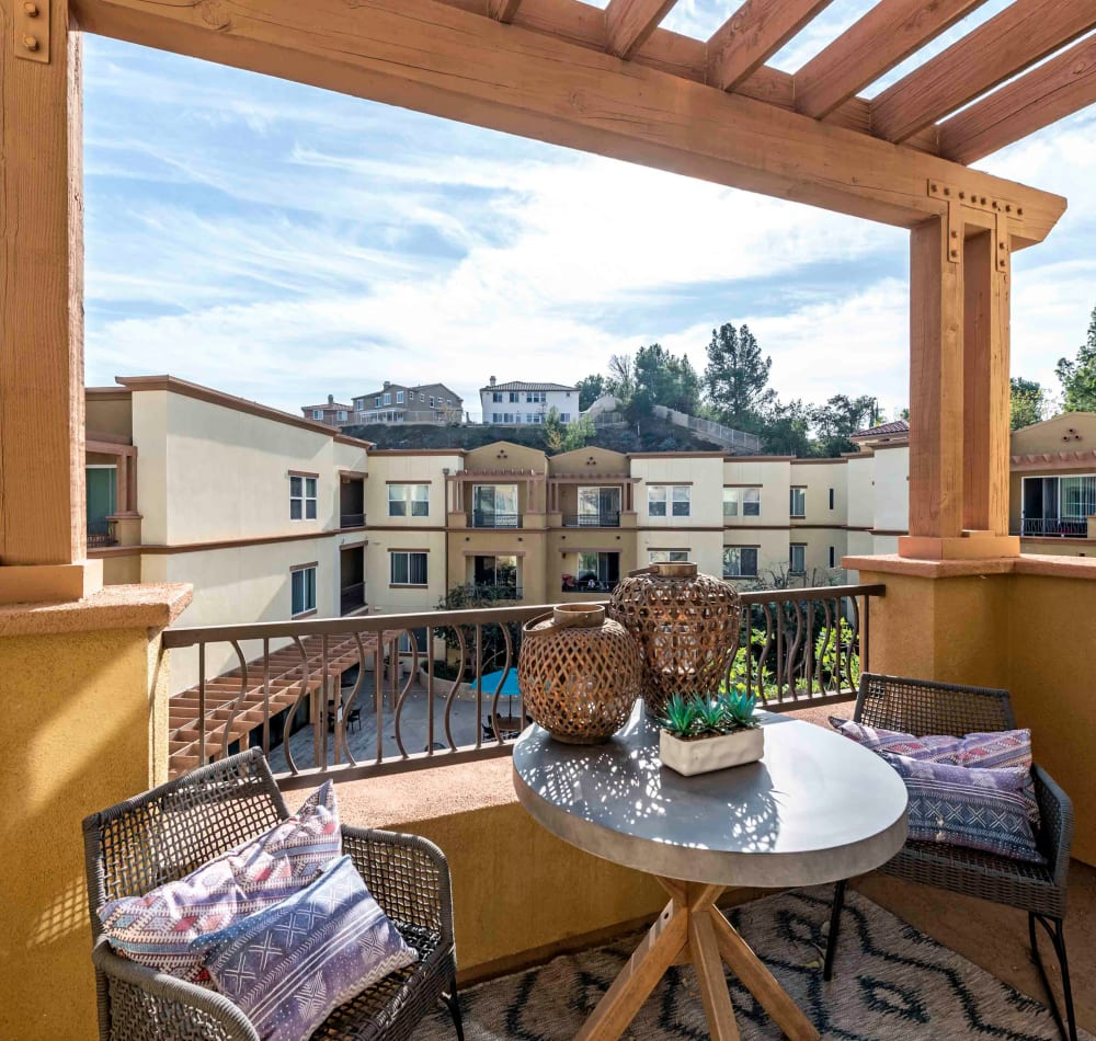 Large private balcony with a pergola above outside an apartment home at Sofi at Topanga Canyon in Chatsworth, California