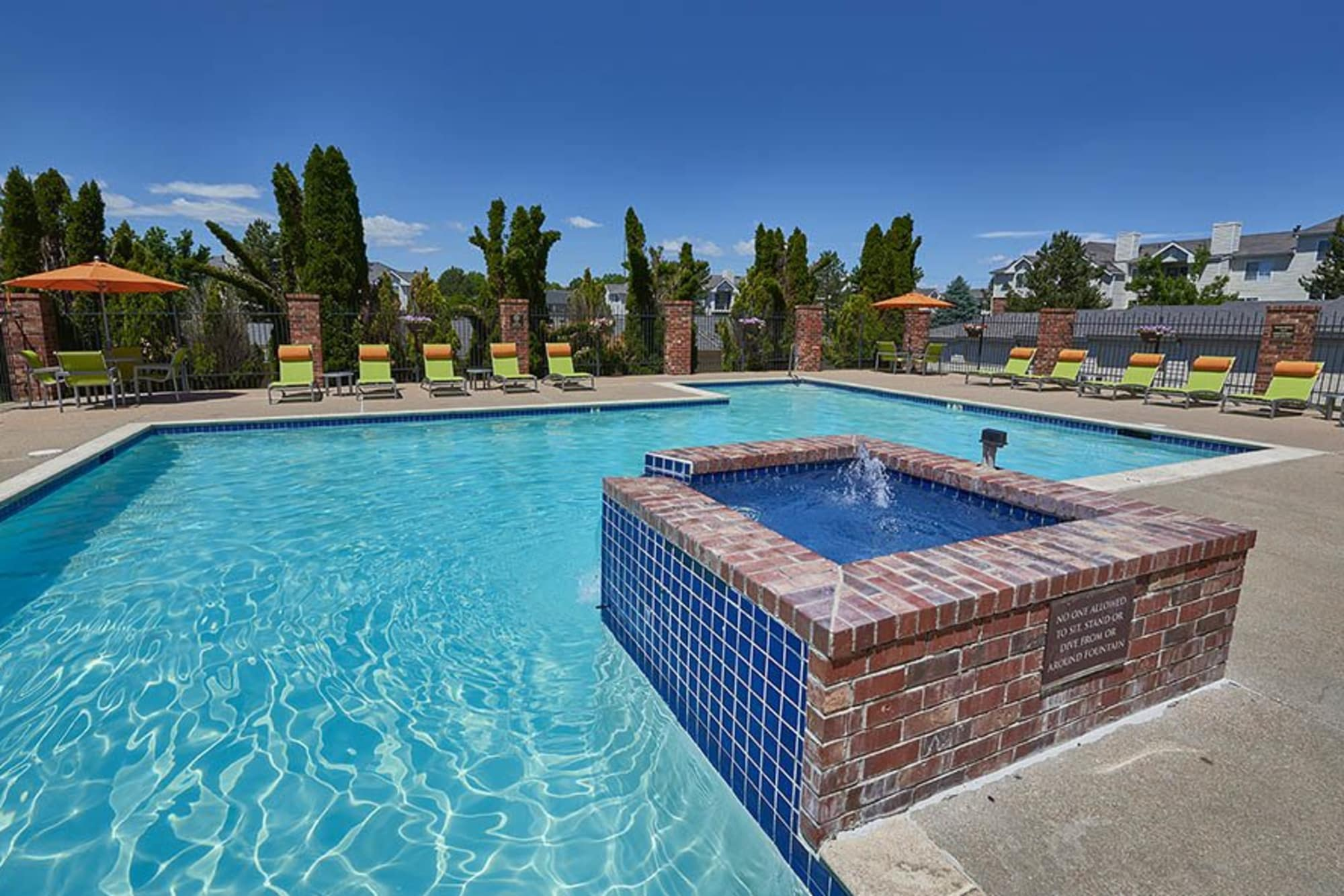 Sparkling pool with fountain and lounge area at Villas at Homestead Apartments