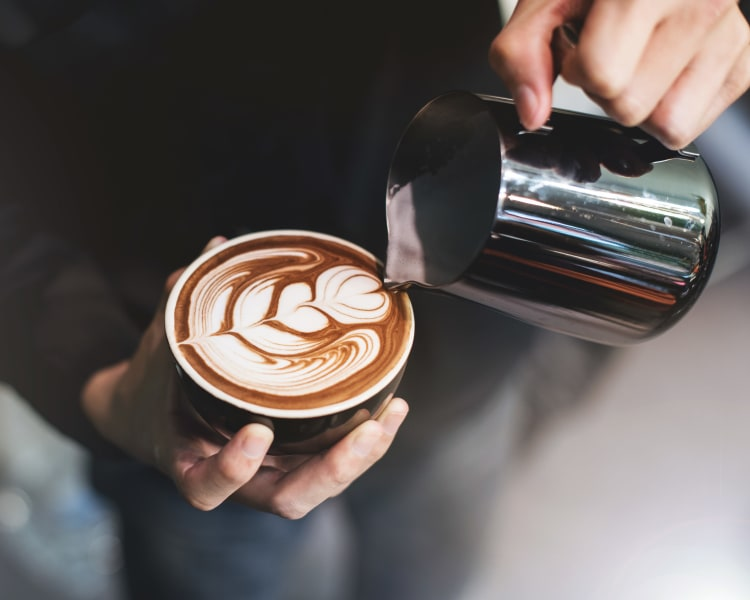 Barista making a latté for a customer near Sofi Westview in San Diego, California