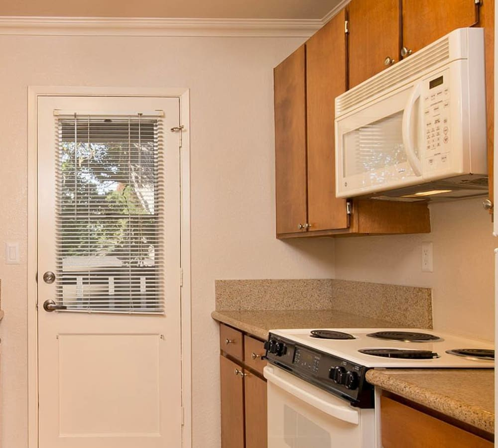 Kitchen with wood-style cabinets and white appliances at Seventeen Mile Drive Village Apartment Homes in Pacific Grove, California