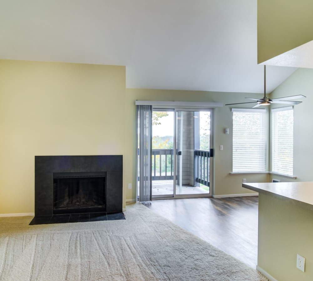 Fireplace near the sliding door to the private balcony outside a model home at Sofi Lake Oswego in Lake Oswego, Oregon