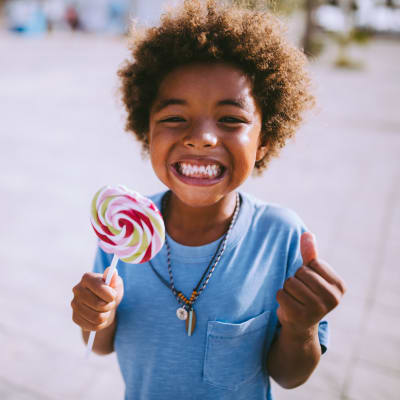 Child smiling with swirl lollipop in his hand at The Marq at Brookhaven in Atlanta, Georgia