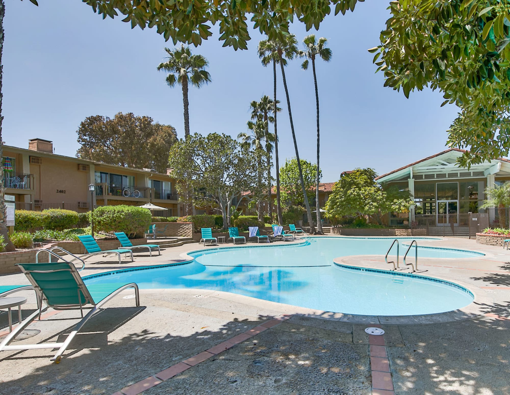 Resort-style swimming pool area with lounge chairs shaded by mature trees at Mediterranean Village Apartments in Costa Mesa, California
