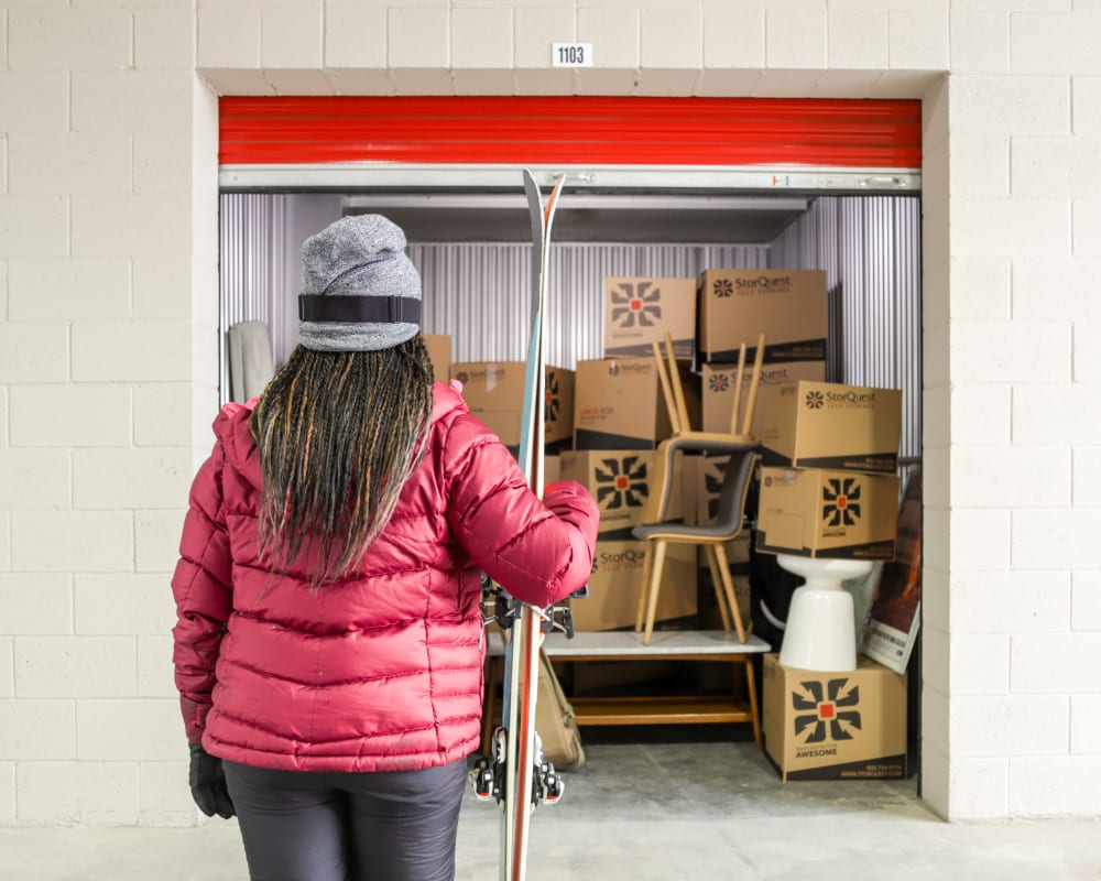 Woman holding skis in front of storage unit full of boxes at StorQuest Self Storage in Santa Monica, California