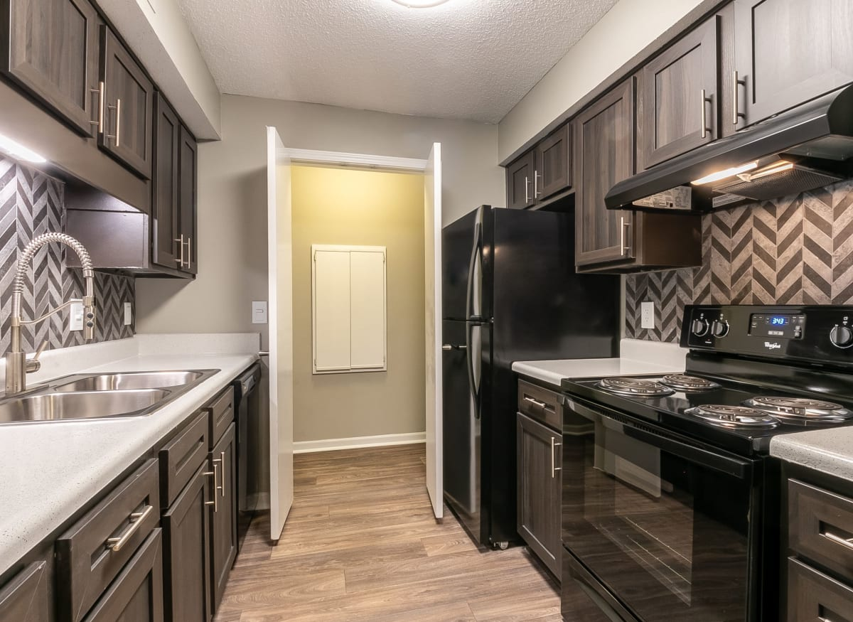 Modern kitchen with black appliances at The Square at Lawrenceville in Lawrenceville, Georgia