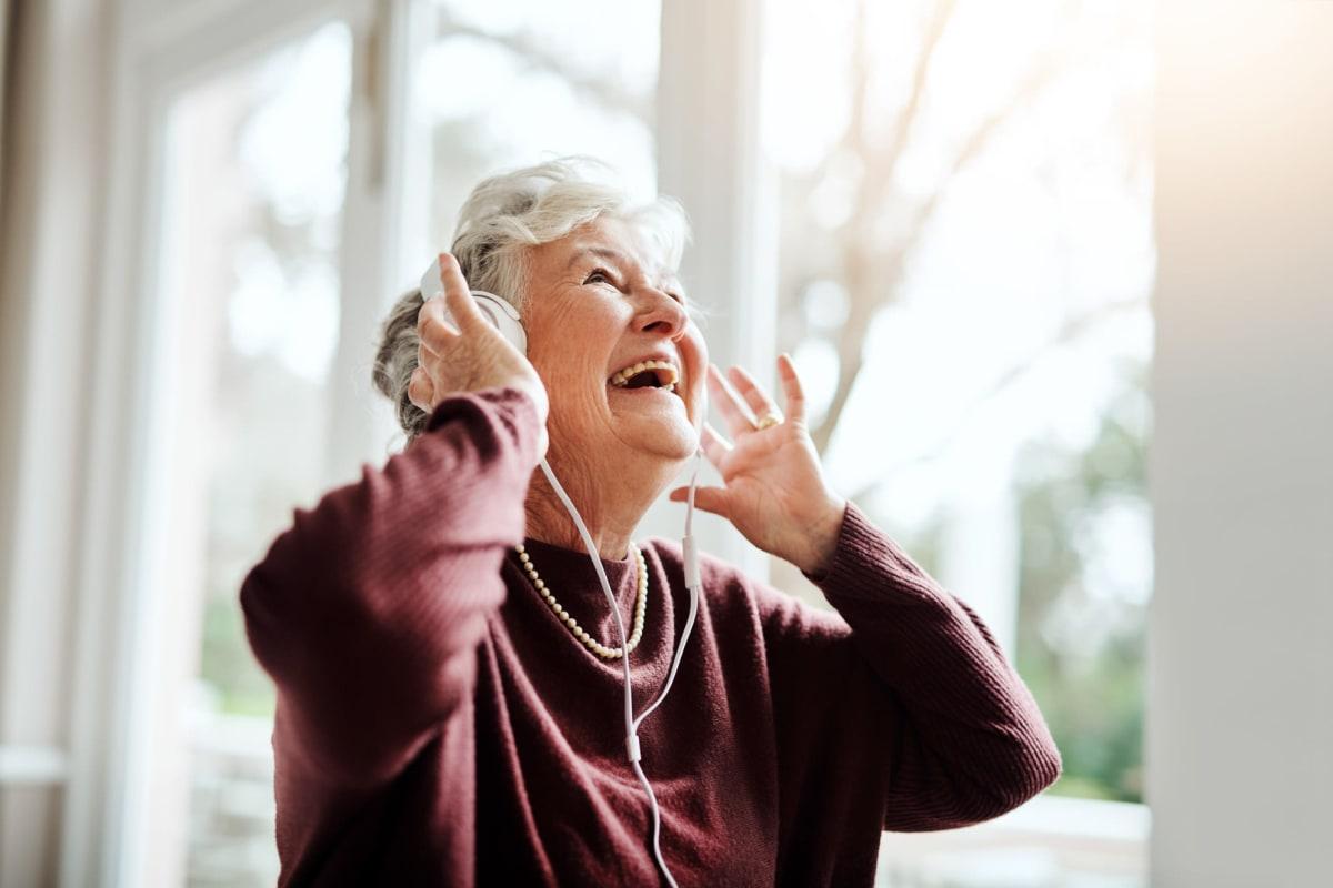 A resident enjoying music through headphones at an Oxford Senior Living location