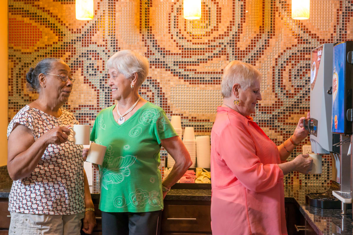A group standing around drinking coffee in the lobby at Isle at Cedar Ridge in Cedar Park, Texas