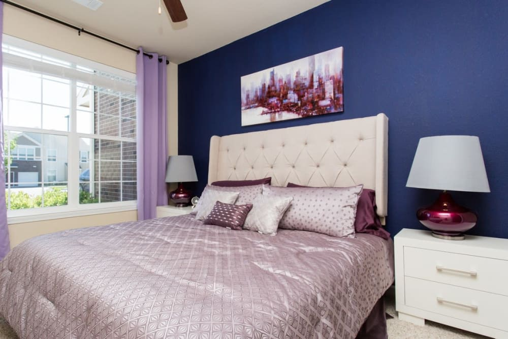 Bedroom with Blue Accent Wall and Large Window at Springs at Egan Drive in Savage, MN