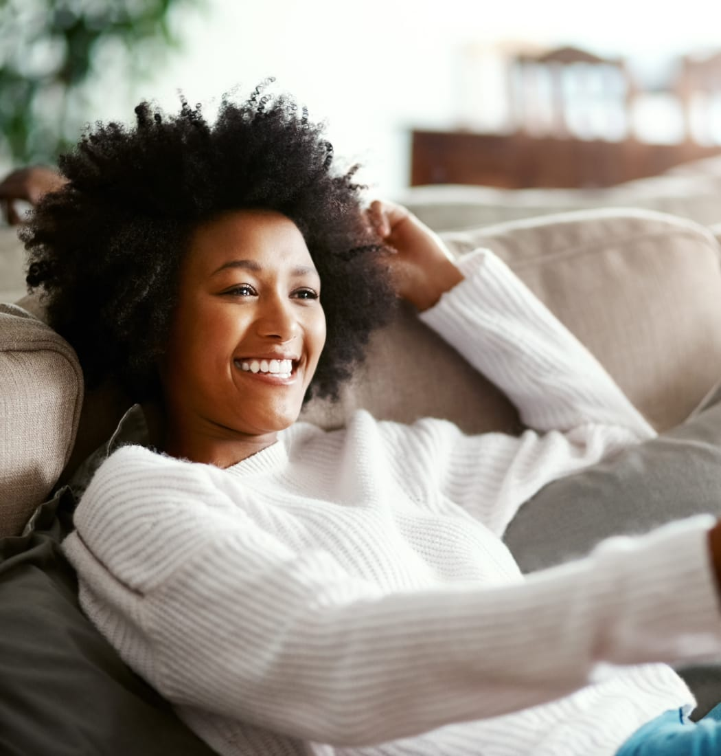 Resident relaxing on her couch at Cedartree Apartments in Santa Clara, California