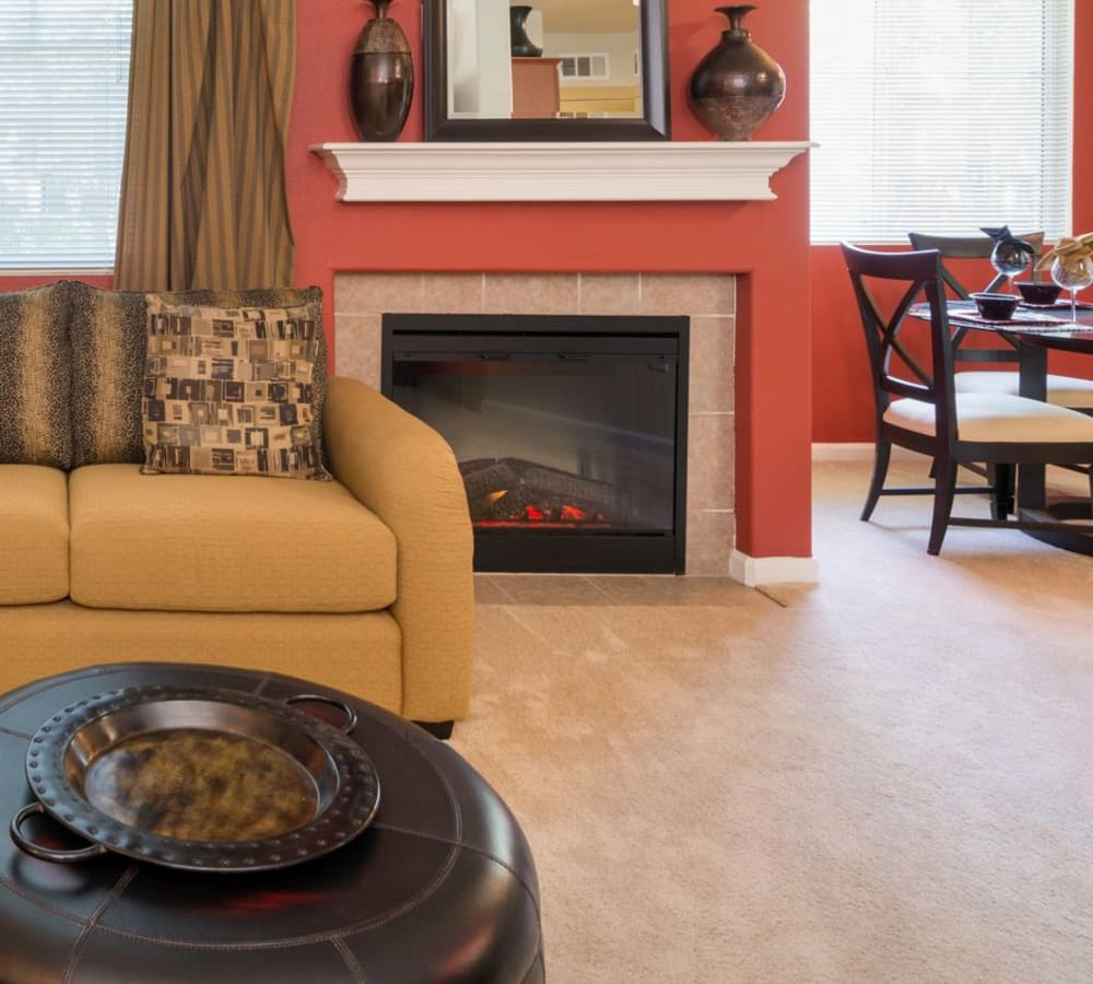 Living room with plush carpeting and a fireplace at The Artisan Apartment Homes in Sacramento, California