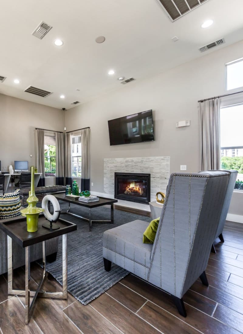 Clubhouse with chairs, a TV, and a fireplace at Marquis at Crown Ridge in San Antonio, Texas