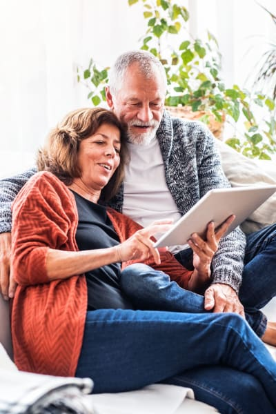 Residents couple surfing the web on a tablet device in their spacious home at The Pointe at Siena Ridge in Davenport, Florida