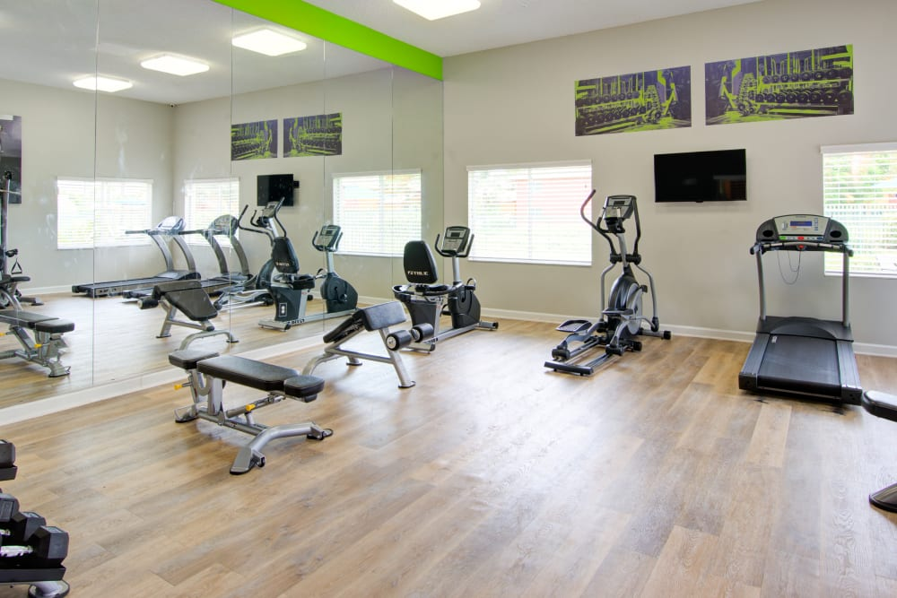 A fitness center with individual workout stations at Running Brook Apartments in Miami, Florida