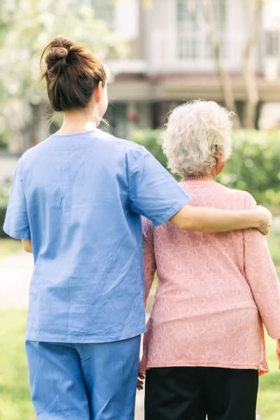 Nurse and resident walking outside at Living Care Lifestyles