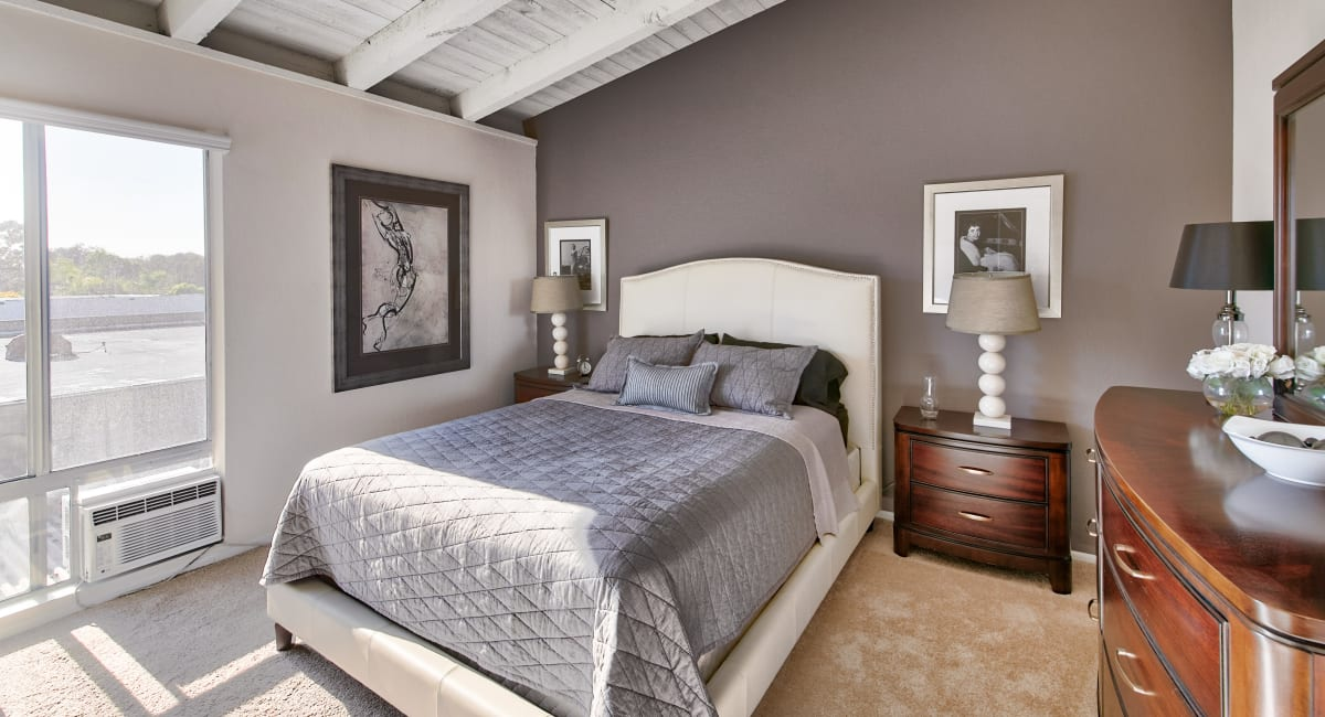 Accent wall and plush carpeting in the primary bedroom of a model apartment at Mediterranean Village Apartments in Costa Mesa, California