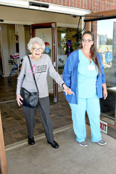A resident walking outside with the help of a staff member at Providence Assisted Living in Senatobia, Mississippi.