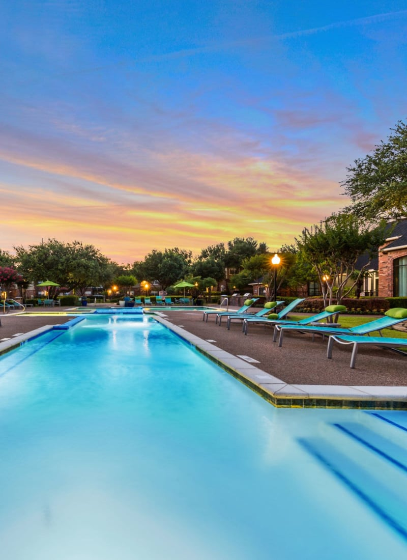 Lighted pool at sunset with sun chairs at Marquis at Stonebriar in Frisco, Texas