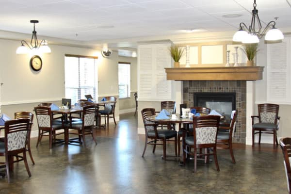 Dining hall with dark stone flooring and tall ceilings at Deephaven Woods in Deephaven, Minnesota