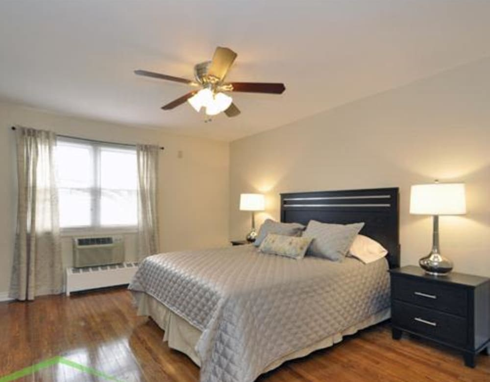 Large bedroom with wood style flooring and a ceiling fan at Eagle Rock Apartments at Maplewood in Maplewood, New Jersey