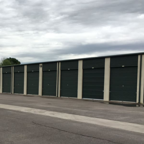 Green doors on outdoor drive-up units at StorQuest Self Storage in Richmond, Texas