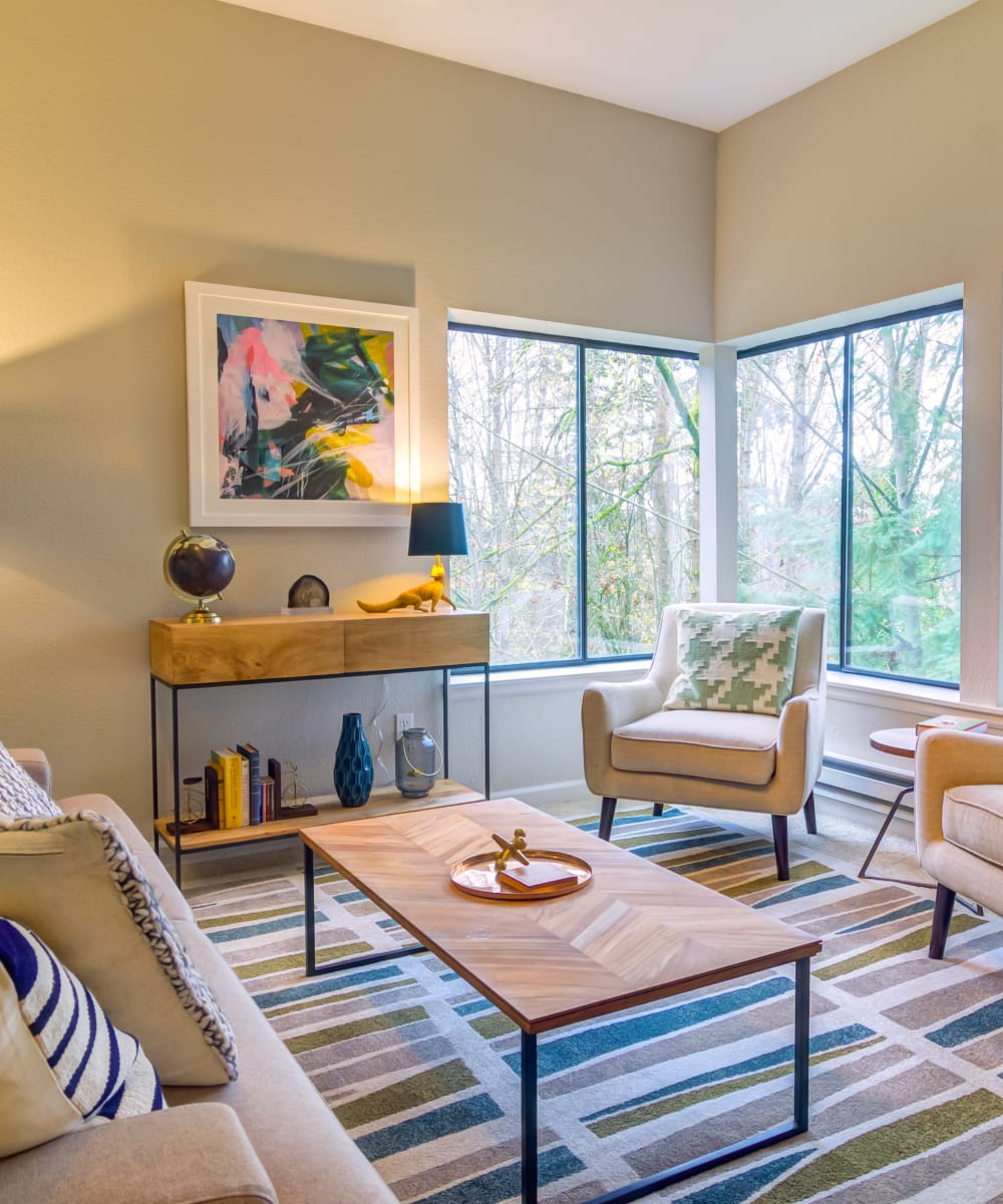 Model home's living area with large bay windows and wooded views at Sofi at Somerset in Bellevue, Washington