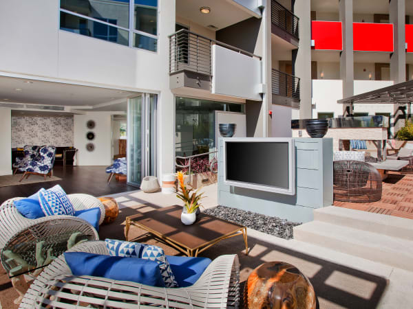 Outdoor lounge with a big-screen TV in the open-air courtyard at Brio Apartment Homes in Glendale, California