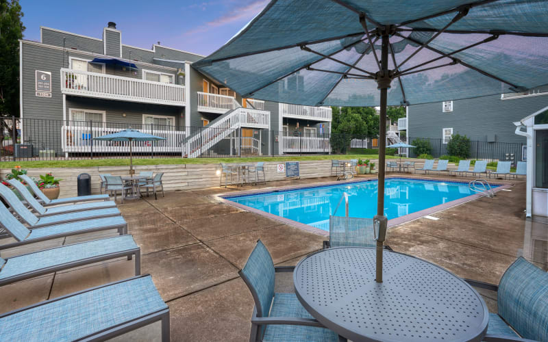 Clubhouse, swimming pool and lounge chairs at dusk at Bluesky Landing Apartments in Lakewood, Colorado