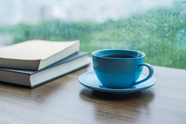 Cup of coffee and some books by a window at at Radiant Senior Living community