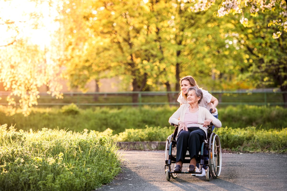 A daughter pushing her mother in a wheel chair around the beautiful grounds at a Meridian Senior Living community
