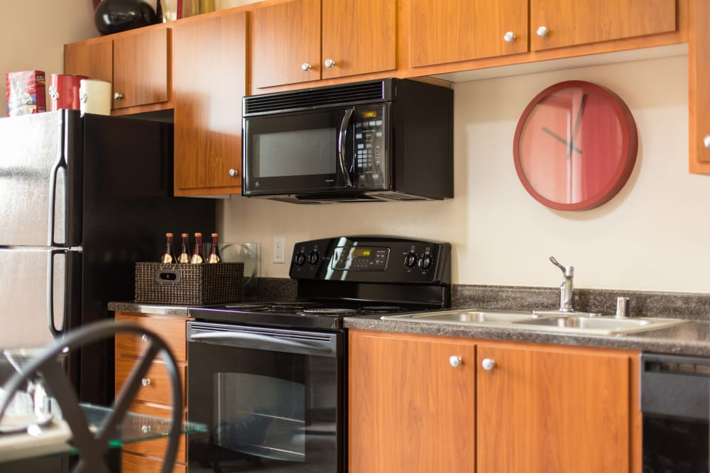Kitchen with black appliances at Venu at Galleria Condominium Rentals in Roseville, California