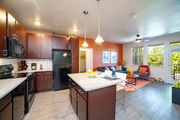 Modern kitchen with granite countertops and hardwood floors in model home at Kapolei Lofts in Kapolei, Hawaii