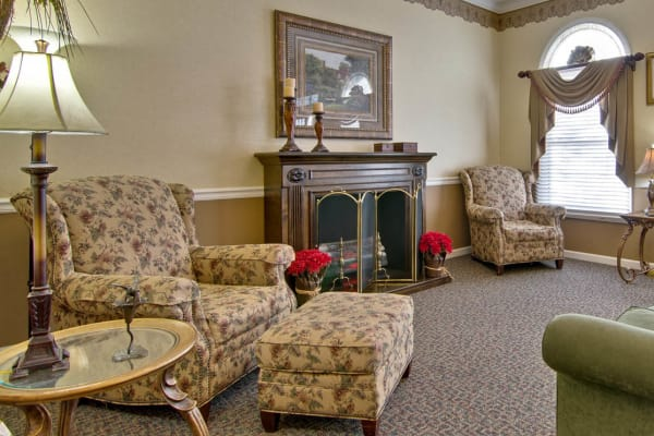 Assisted living lounge  with fireside seating at Eiffel Gardens in Paris, Tennessee