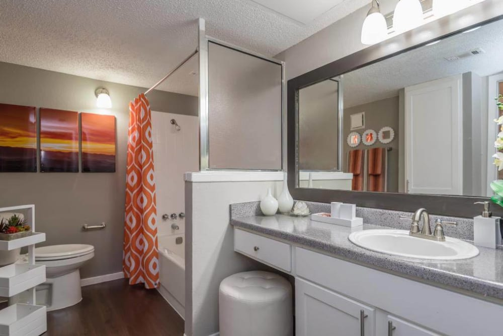 Spacious bathroom with large mirror and vanity area at The Carling on Frankford in Carrollton, Texas