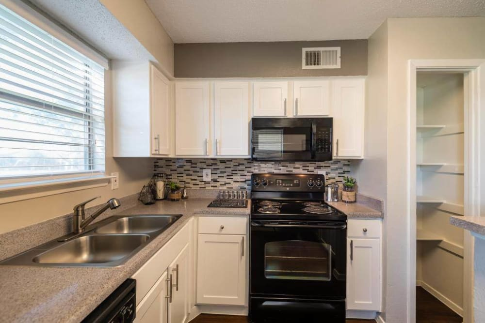 Kitchen wiht white cabinets and black appliances for a modern look at The Carling on Frankford in Carrollton, Texas