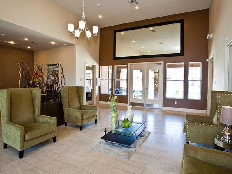 A lobby with green chairs at Monterra Apartment Homes