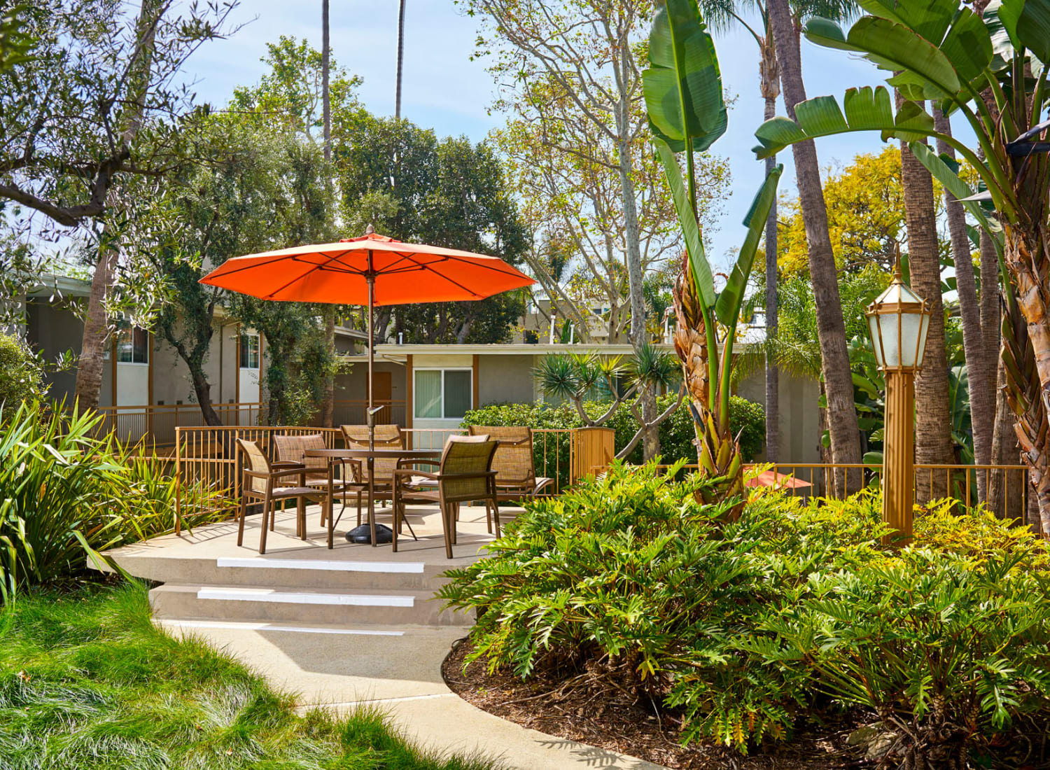 Shaded seating area surrounded by lush flora at West Park Village in Los Angeles, California
