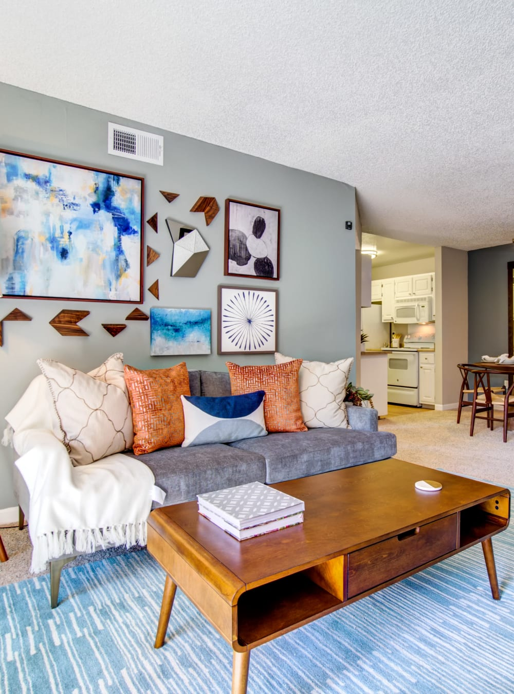Retro-modern furnishings and an accent wall in a model home's living area at Waterstone Fremont in Fremont, California